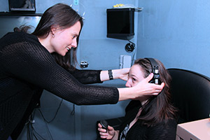 Audiologist placing headphones on a girl