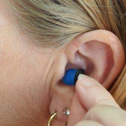 Woman inserts earplug into her ear.
