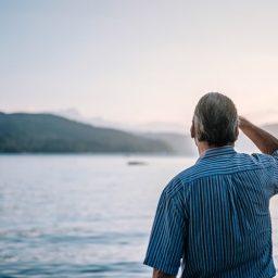 Older man staring out at a lake.